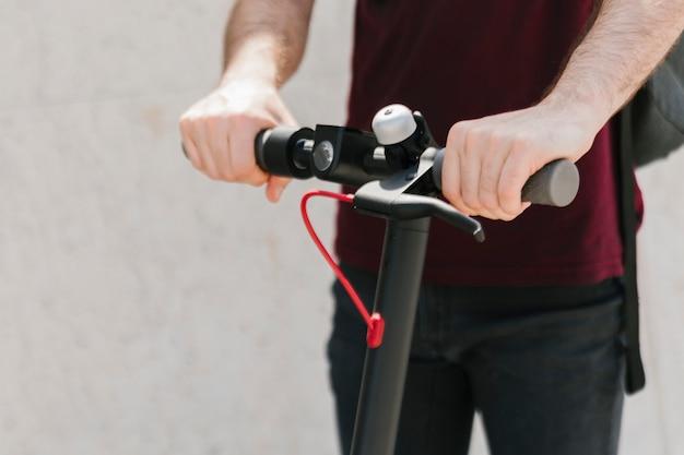 Close-up piloto e-scooter com fundo desfocado Foto gratuita