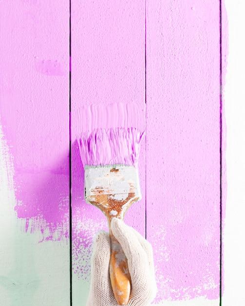 Close up pintor homem mão pintando a cor rosa na mesa de prancha de madeira com espaço de cópia, interior de design criativo brilhante e como pintar a superfície de madeira. Foto Premium