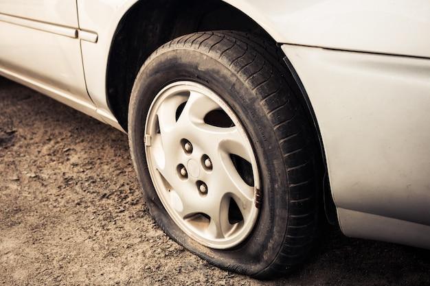 Close-up pneu e carro velho na estrada à espera de reparação Foto Premium