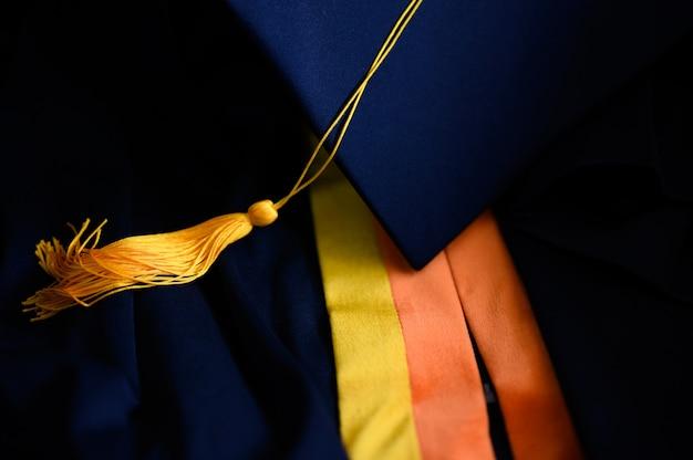 Close-up preto chapéu de formatura e borla amarela colocada no chão Foto Premium