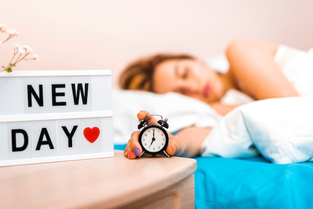 Close-up relógio segurar por uma mulher com sono Foto gratuita