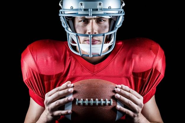 Close-up, retrato, de, confiante, jogador football americano, segurando bola Foto Premium