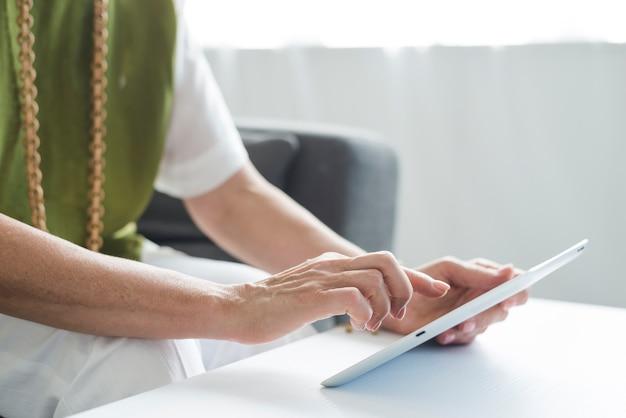 Close-up, sênior, mulher, mão, usando, tablete digital Foto gratuita