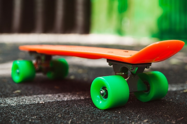 Close-up skate centavo laranja no asfalto atrás da parede verde Foto gratuita
