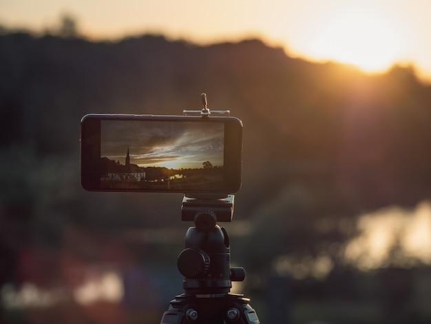 Close-up smartphone tira uma foto de paisagem e vídeo timelapse no tripé de suporte no pôr do sol. Foto Premium