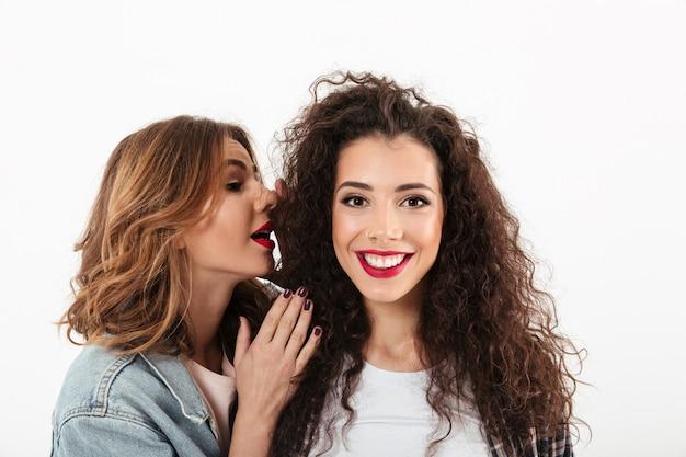 Close-up sorridente menina encaracolada, olhando para a câmera enquanto sua amiga falando no ouvido sobre parede branca Foto gratuita