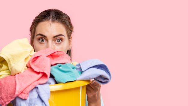 Close-up, surpreendido, mulher, com, cesta lavanderia Foto gratuita