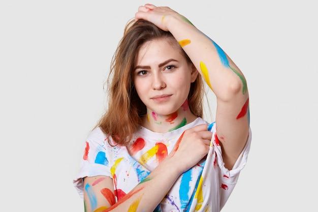 Close-up tiro da atraente jovem artista feminina, manchou as roupas com tintas depois de fazer desenhos coloridos, tem um olhar sério para a câmera Foto gratuita