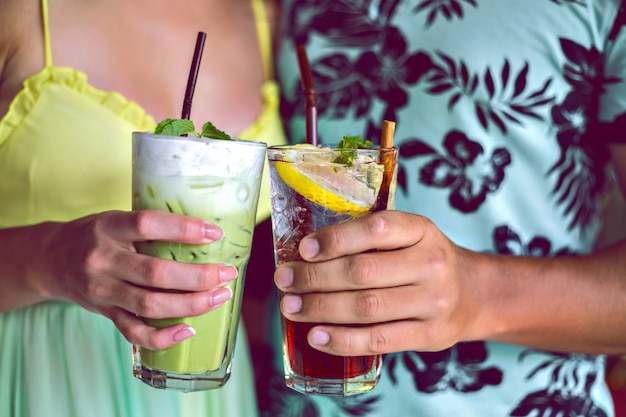 Close-up tiro de jovem casal sorridente desfrutar de suas bebidas, fazendo elogios para a câmera, matcha latte e limonada berry, coquetéis na festa, cores brilhantes em tons. Foto gratuita