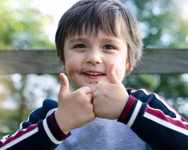 Close-up tiro de menino de escola com o rosto sujo com sorvete de chocolate, criança adorável sorrindo com desarrumado boca de chocolate e mostrando dois dedos, garoto bonito desistindo polegar como sinal de sucesso Foto Premium