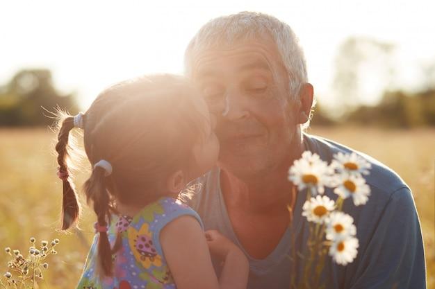 Close-up tiro de pequeno neto abraço e beija o avô que dá para fotos camomiles, caminhar juntos no campo Foto gratuita