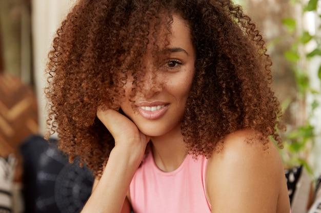 Close-up tiro de uma mulher atraente com cabelo encaracolado e pele escura, tem uma expressão positiva, passa o tempo livre no círculo familiar. aluna de pele escura descansando após um dia cansativo na universidade Foto gratuita
