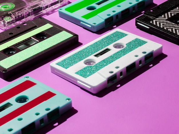 Close-up tiro fitas cassete vibrantes em fundo rosa Foto gratuita