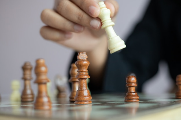 Close-up tiro mão de mulher de negócios jogando o tabuleiro de xadrez para vencer, matando o rei da metáfora do adversário vencedor da competição de negócios e perdedor selecione foco profundidade de campo Foto Premium