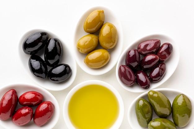 Close-up vermelho preto amarelo roxo azeitonas em pratos com folhas e pires de oliveira Foto gratuita