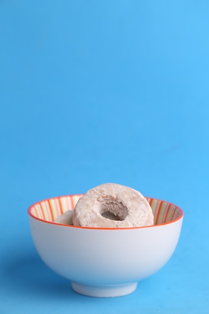Close up vertical de uma tigela de biscoitos caseiros com açúcar em pó contra um fundo azul Foto gratuita