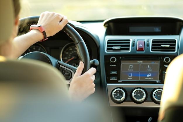 Close-up vista das mãos de mulher segurando o volante, dirigindo um carro na rua da cidade em dia ensolarado. Foto Premium