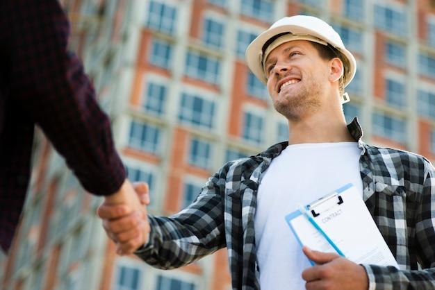Close-up, vista de ângulo baixo do engenheiro e arquiteto apertando as mãos Foto gratuita