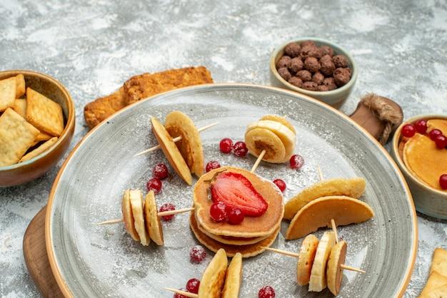 Close-up vista de deliciosas panquecas, biscoitos e bolos no café da manhã em uma tábua de cortar em azul Foto gratuita