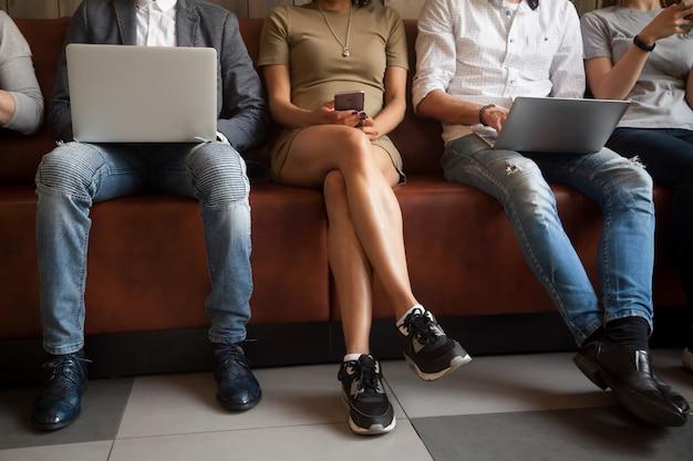 Close-up vista de diversas pessoas sentadas usando dispositivos eletrônicos Foto gratuita