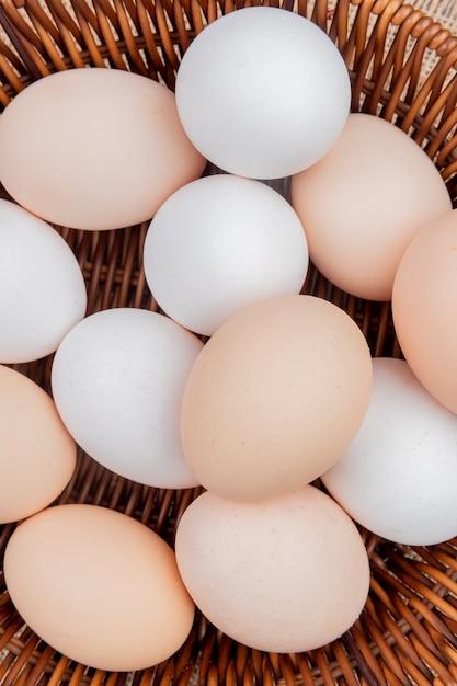 Close-up vista de ovos de galinha em um balde no fundo de pano de saco Foto gratuita