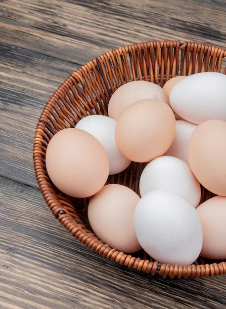 Close-up vista de ovos de galinha fresca em um balde em um fundo de madeira Foto gratuita