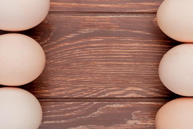 Close-up vista de ovos de galinha fresca em um fundo de madeira com espaço de cópia Foto gratuita