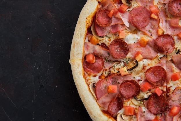 Close-up vista de pizza com presunto, bacon, salsicha, tomate e champignon Foto Premium