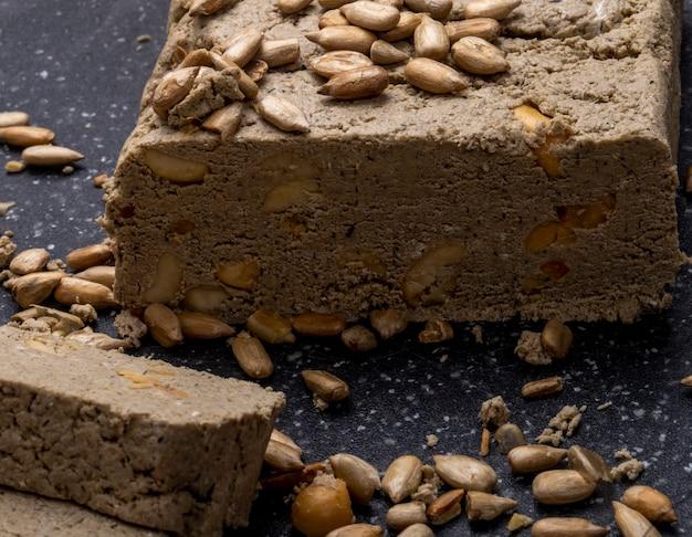Close-up vista de saborosas fatias de halva com sementes de girassol em um quadro negro Foto gratuita