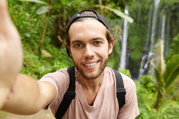 Close-up vista de um alpinista caucasiano bonito usando snapback olhando com um sorriso feliz enquanto tira uma selfie com uma paisagem incrível com cachoeira Foto gratuita