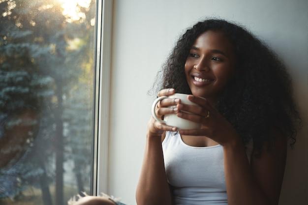 Close-up vista de uma elegante jovem afro-americana com uma blusa branca, descansando dentro de casa, segurando uma xícara grande de chá quente, sorrindo amplamente, sonhando acordada, passando um bom tempo em casa sozinha Foto gratuita