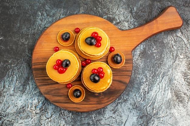 Close-up vista de uma pilha de deliciosas panquecas na tábua de corte em cinza Foto gratuita