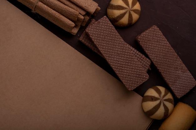 Close-up vista do caderno com cookies diferentes em torno de bolinhos de gengibre e palitos crocantes no escuro Foto gratuita