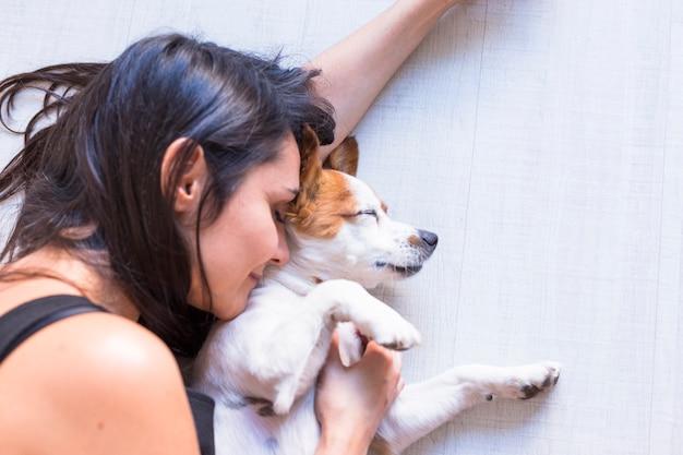 Close-up vista do cão deitado no chão com seu dono. mulher com os olhos fechados. estilo de vida dentro de casa e amor pelo conceito de animais Foto Premium