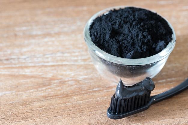 Close-up vista do creme dental de carvão preto e íon de escova de dentes de madeira Foto Premium