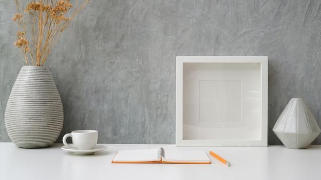 Close-up vista do espaço de trabalho com notebook aberto, xícara de café, moldura e vasos de cerâmica na mesa branca com parede cinza loft Foto Premium