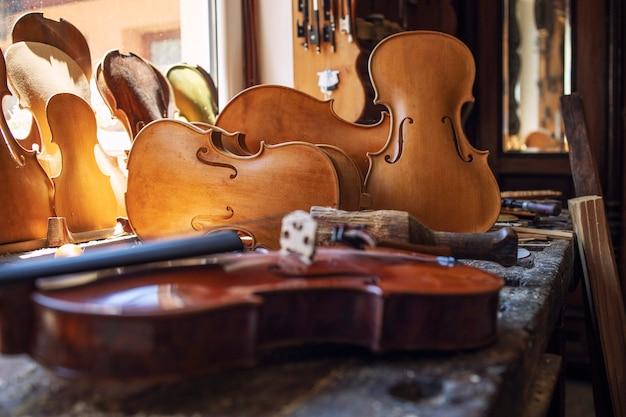Close-up vista do instrumento musical de violinos na oficina. Foto Premium