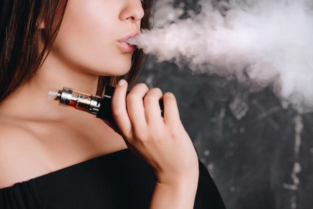 Close-up vista encantadora jovem mulher com cabelo curto, fumando um cigarro, nuvem de vapor. Foto Premium