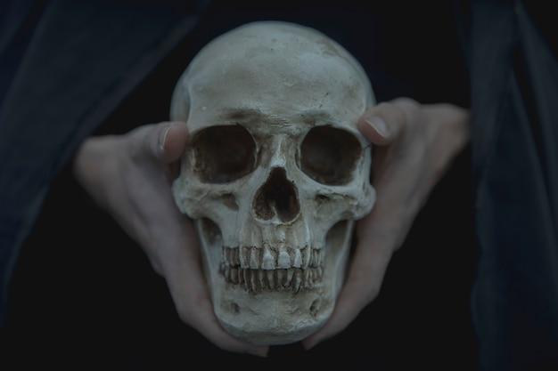 Close-up vista frontal do crânio sendo realizada pelo homem Foto gratuita