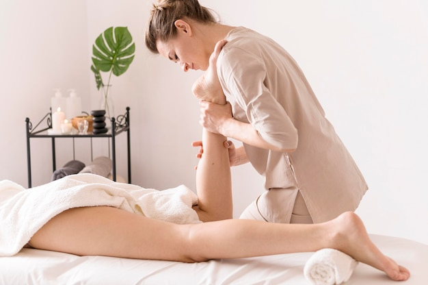 Close-up vista lateral para massagem no tornozelo Foto gratuita