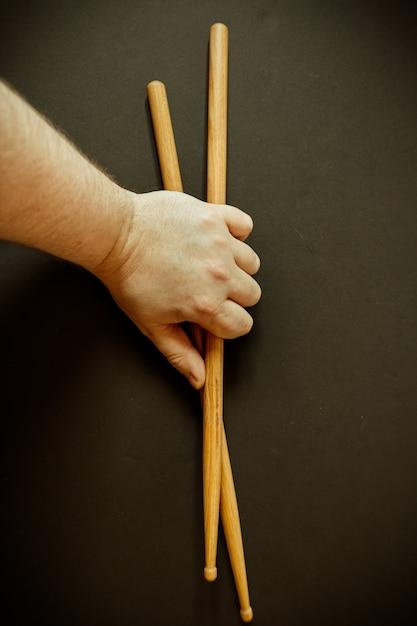 Close vertical da mão de uma pessoa segurando duas baquetas em uma superfície preta Foto gratuita