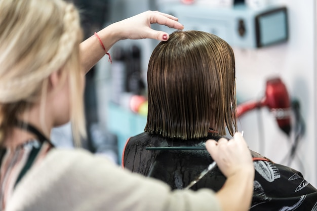 Close vertical de um cabeleireiro cortando o cabelo curto de uma mulher em um salão de beleza Foto gratuita