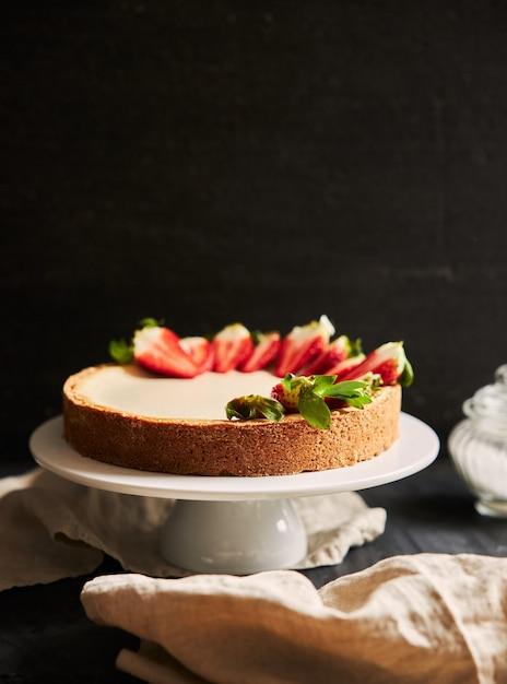 Close vertical de um cheesecake de morango em um prato branco Foto gratuita