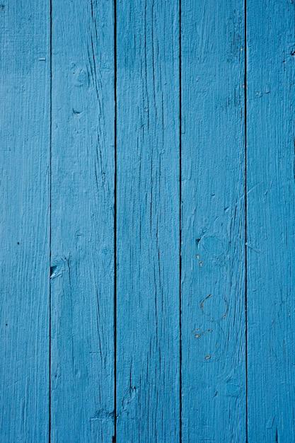 Close vertical de uma parede de madeira pintada de azul sob as luzes Foto gratuita