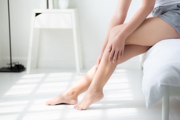 A imagem mostra as pernas de uma mulher branca. A mulher está cuidando da sua pele, sentada na ponta da cama com as pernas próximas ao chão. Ela passa as duas mãos na perna esquerda, que está um pouco dobrada, enquanto a perna direita está esticada. Ao fundo, podemos ver a luz do sol projetada no chão do quarto.