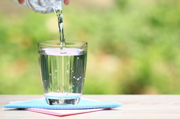 Closeup copo de água no fundo da natureza de mesa Foto Premium