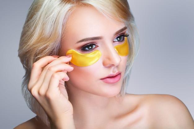Closeup da bela mulher sorridente feliz com hidratante sob máscara de olho Foto Premium