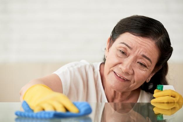 Closeup da empregada doméstica polir mesa de vidro com limpador de spray de vidro Foto gratuita