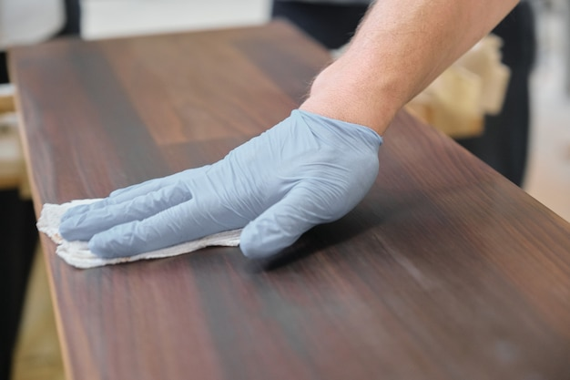 Closeup da mão do trabalhador em luvas de proteção com tampa de acabamento Foto Premium