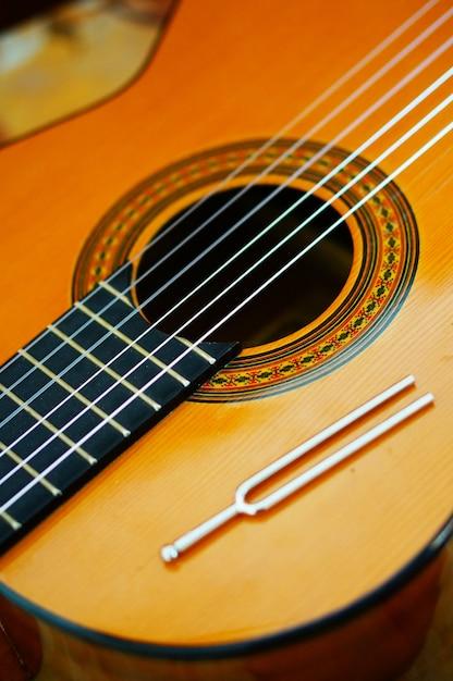 Closeup de alto ângulo vertical das cordas de uma guitarra clássica Foto gratuita